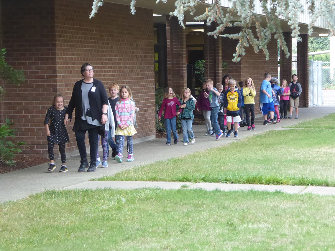 Students walking in a line on a sidewalk next to the school