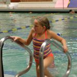 girl climbing ladder out of pool