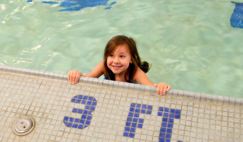 girl smiling at camera near 3 foot pool sign